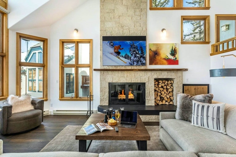 Cozy Beaver Creek home rental with fireplace, sofa and coffee table.