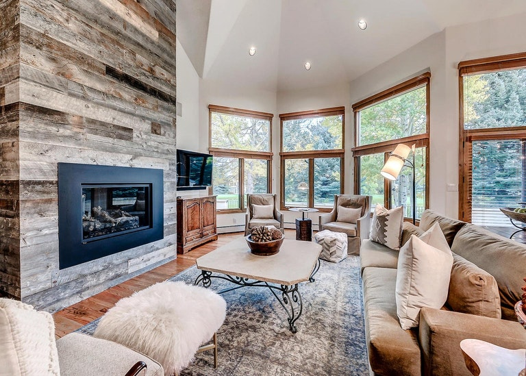 Luxurious lounge of a home rental in Beaver Creek with fireplace and large windows.