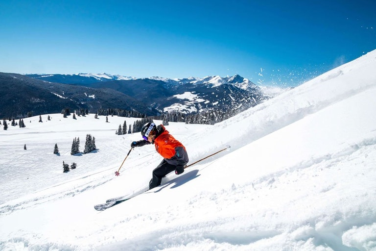 Lady skiing in Vail Valley with mountains in background