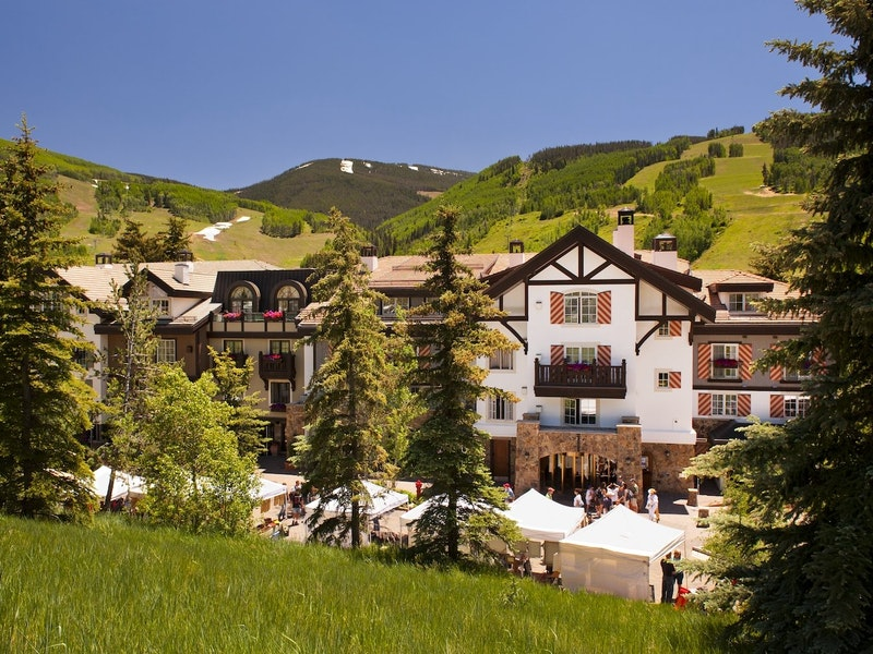 Vail condo rental European style building with lush green mountains in the background.