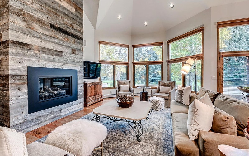 Luxurious lounge of a home rental in Beaver Creek resort with large modern fireplace and large windows.