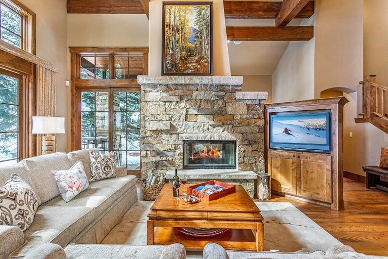 Beaver Creek rental option lounge with couches, wooden coffee table, fireplace and large windows.