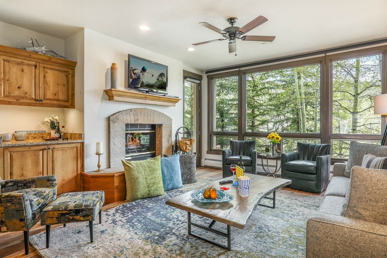 Beaver Creek rental option lounge with couches, armchairs, a fireplace and large windows looking out onto treetops.