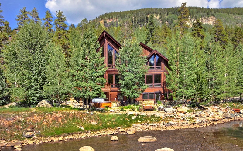 3 Peaks River Retreat: A wooden cabin nestled between trees on the edge of a river bank.