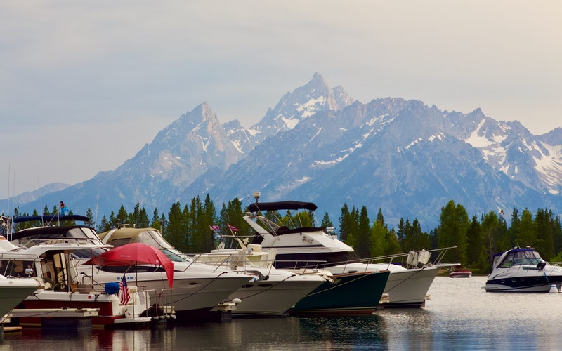 Boats on a lake with trees and snowy mountains in the background at Jackson Hole.