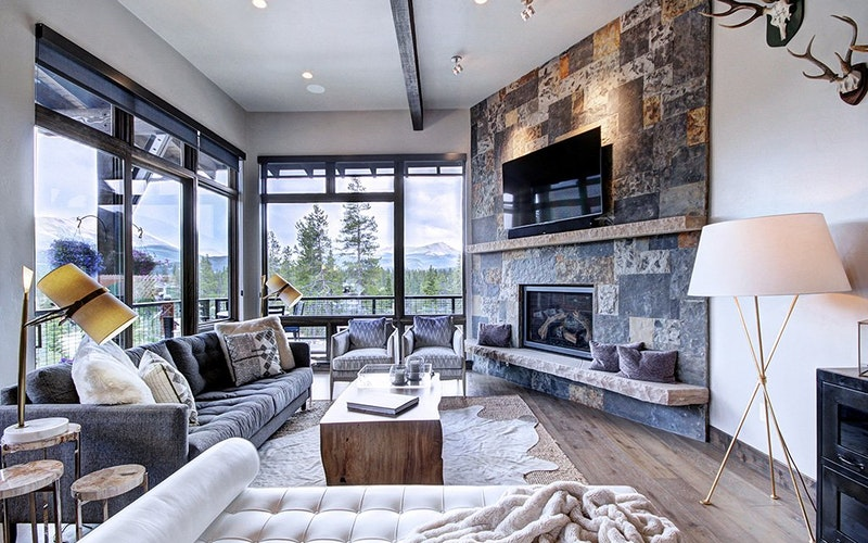 Modern lounge of Gondola Overlook with couches, fireplace, a tv and large windows.