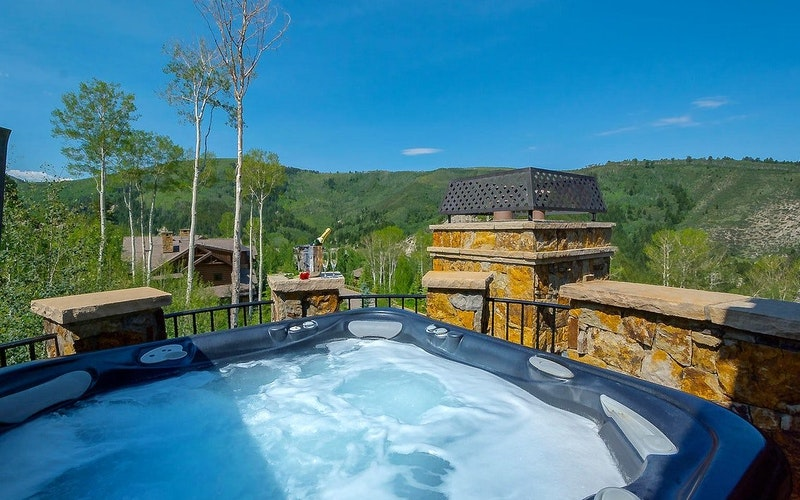 Hot tub overlooking a valley with lush green hills in the background.