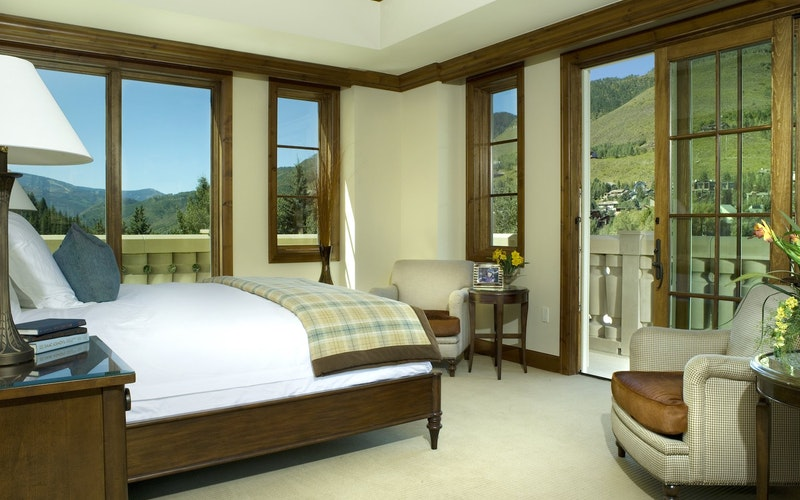 Master bedroom of The Ritz looking out onto green mountains.