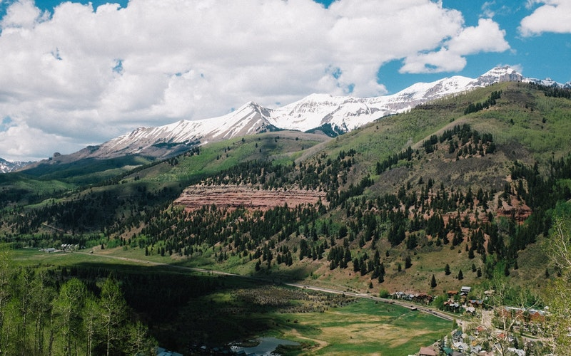 Green Telluride mountainside with snowcapped mountains in the distance.