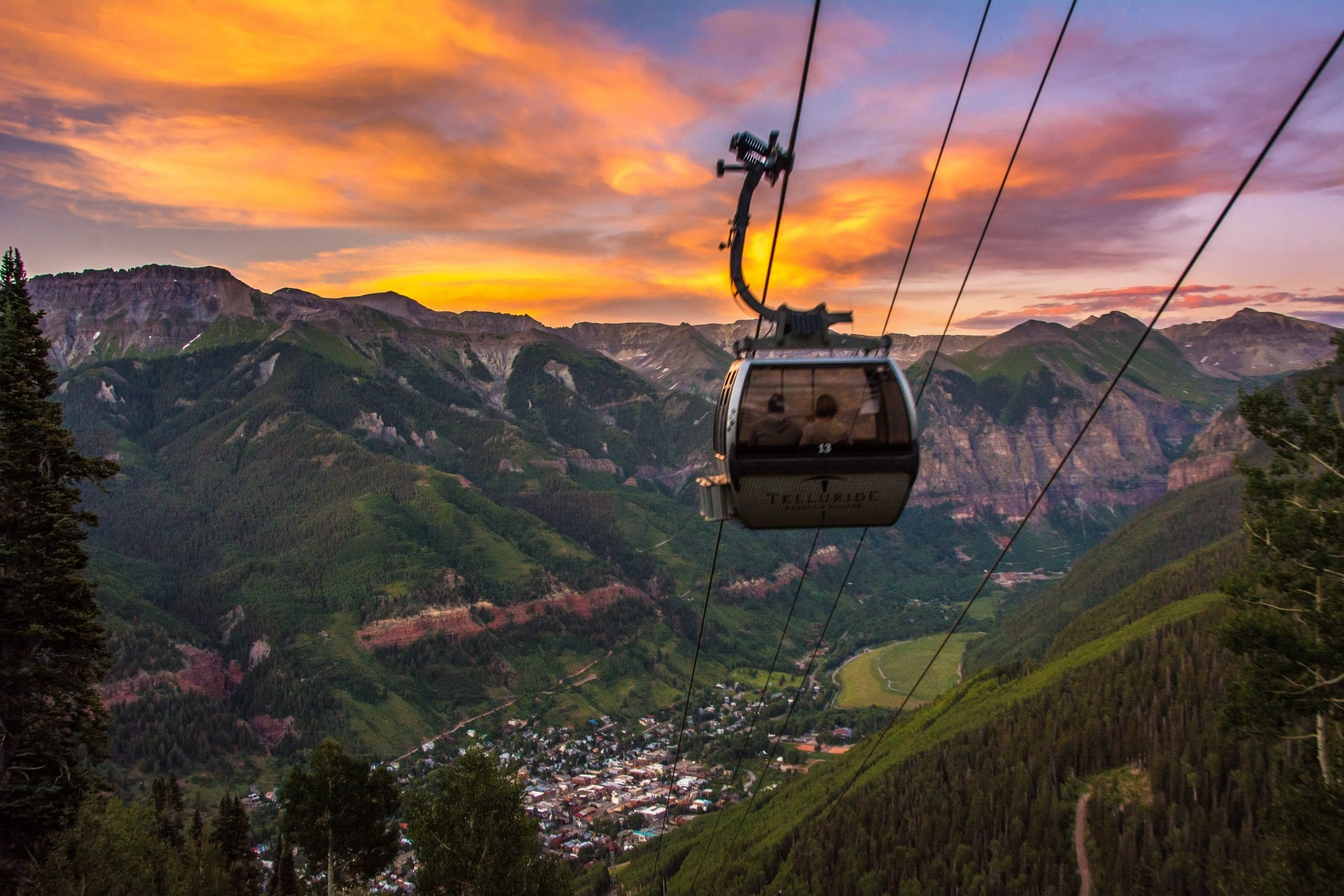 A gondola looking down over Telluride with a beautiful sunset in the background.