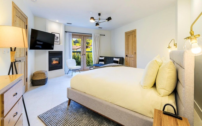 Luxurious bedroom with fireplace, TV and balcony at Peaks Penthouse 741 in Telluride Mountain Village.