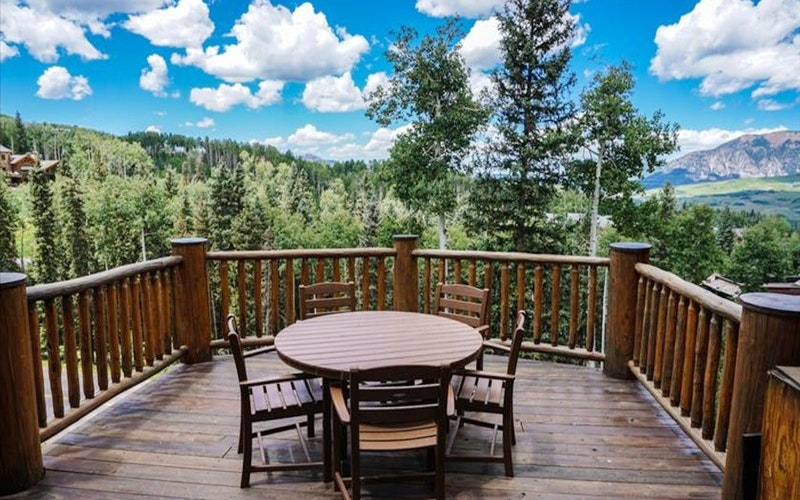 Wooden patio and table overlooking valley with many trees at a Telluride vacation rental.